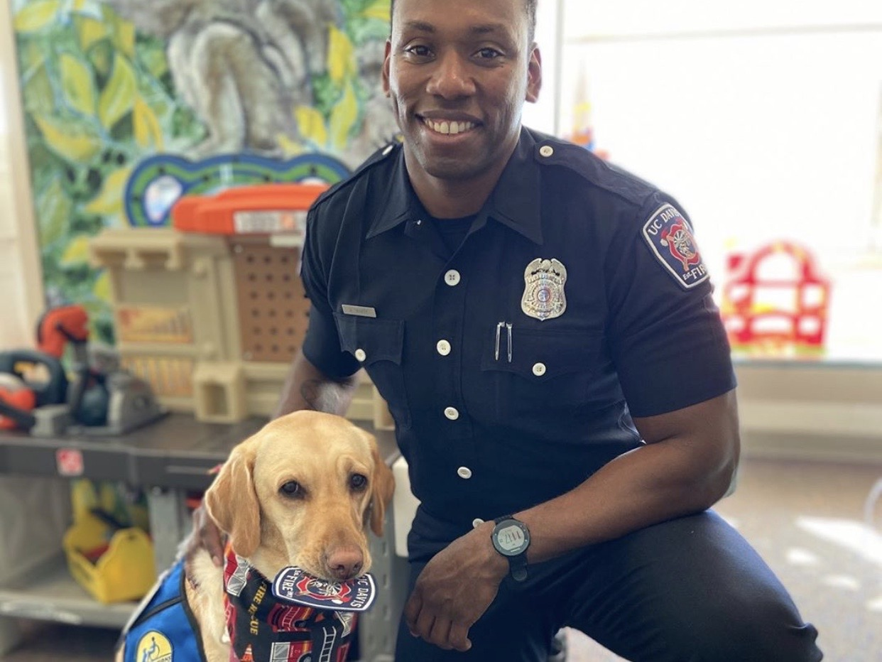 UC Davis Firefighter Avery White with Paloma, the UC Davis Children's Hospital facility dog.
