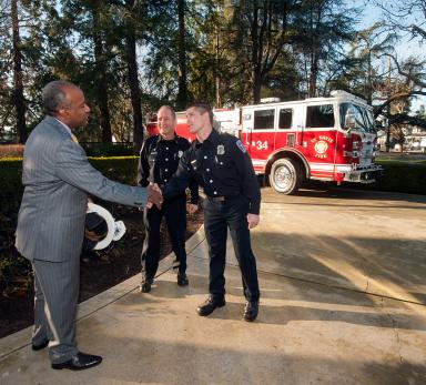 Chancellor Gary S. May greets firefighter Kyle Dubs (shaking hands) and Capt. Joe Newman before breakfast Feb. 2. The Fire Department gave the chancellor a fire helmet. (Gregory Urquiaga/UC Davis)