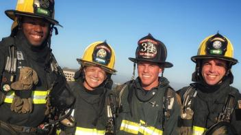 Firefighters wearing helmets and smiling