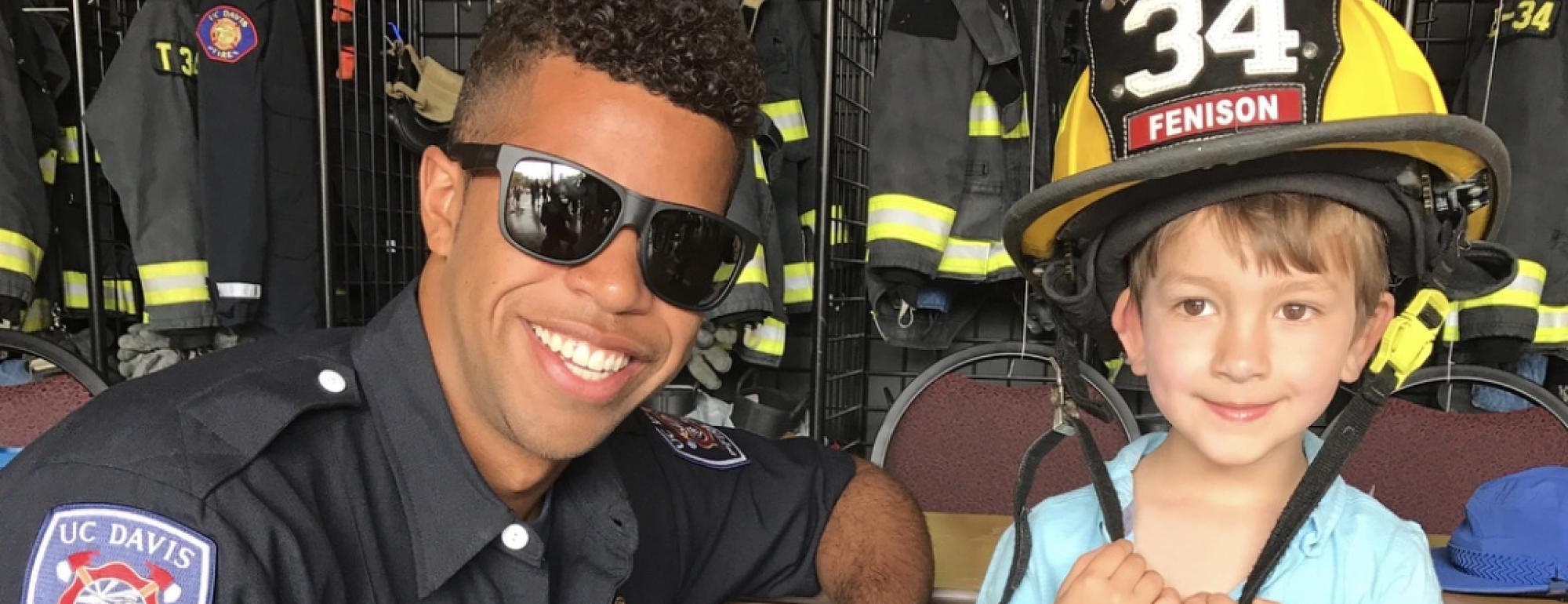 Student Firefighter with young station visitor