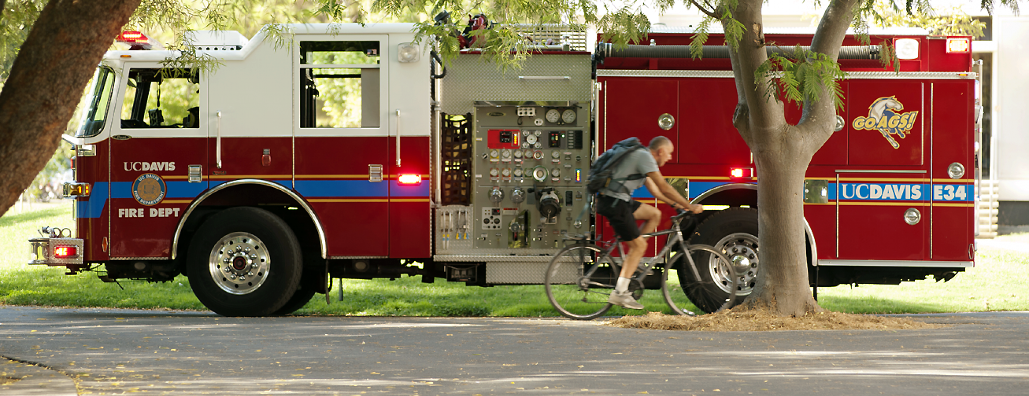 UC Davis Fire Department Engine 34 with bicyclist riding by.