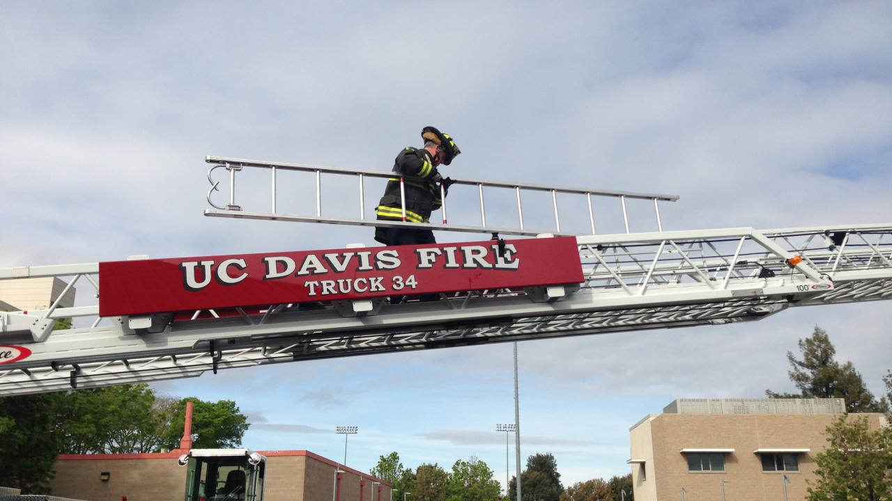 UC Davis Firefighter climbing aerial ladder