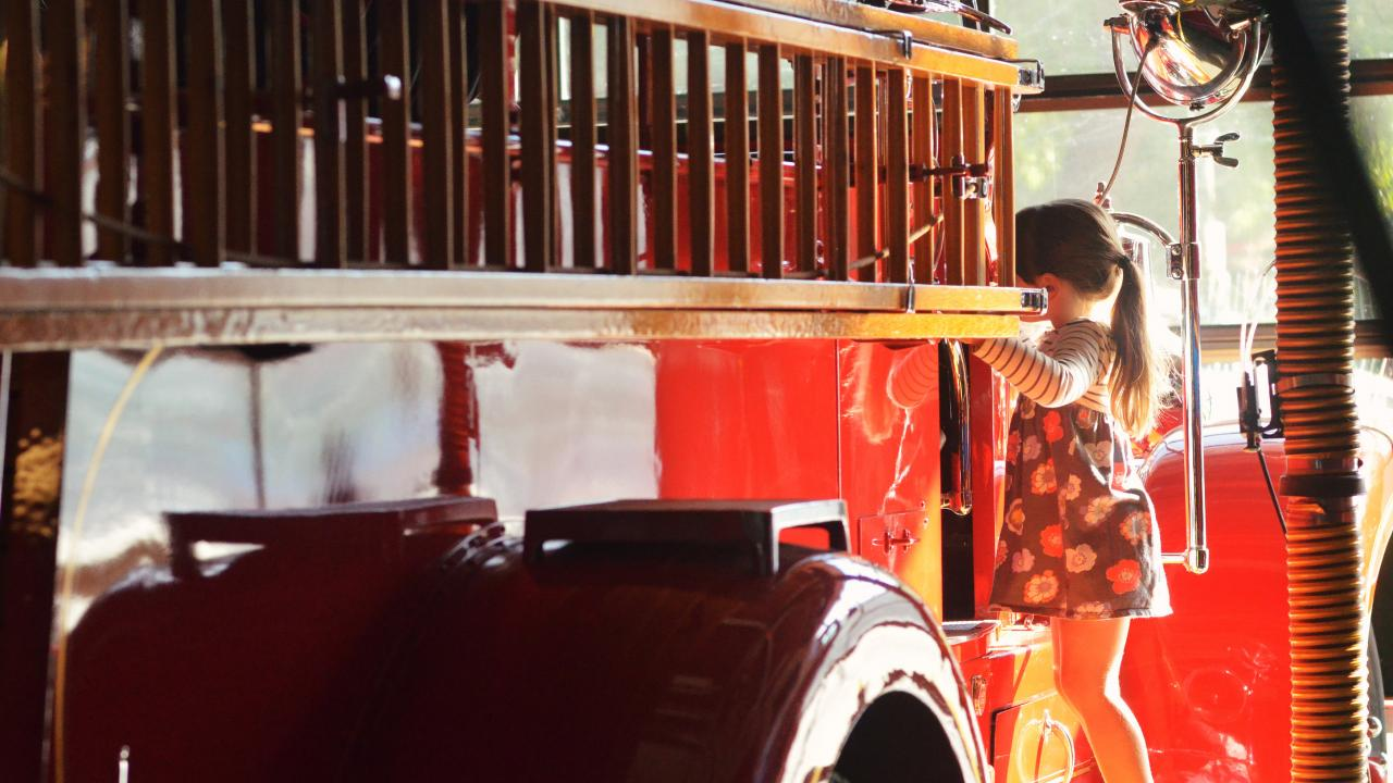 A little girl explores the UC Davis Fire Department's antique fire engine.