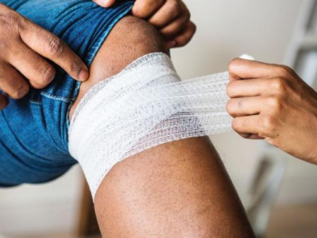 person wrapping bandage below knee