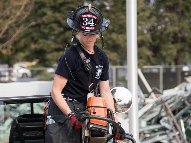 UC Davis Firefighter Corrie Beall placing a chain saw back on Truck 34.