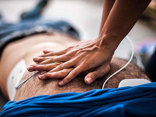 Photo of person performing CPR.