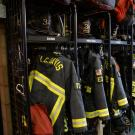 UC Davis Fire Department turnouts hanging on racks at the fire station.