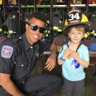 UCDFD Student Firefighter with child in a fire helmet.